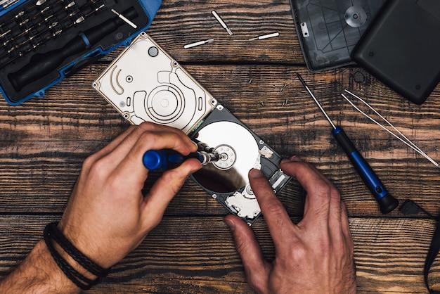 Dwie ręce ze śrubokrętem zdemontuj dysk twardy