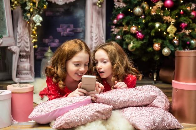 Dwie redhaired siostry w pobliżu drzew noworocznych patrząc na telefon boże narodzenie
