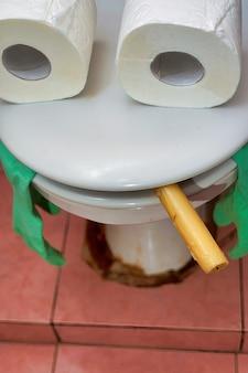 Dwie rolki papieru toaletowego na pokrywie toalety przypominają ludzką głowę
