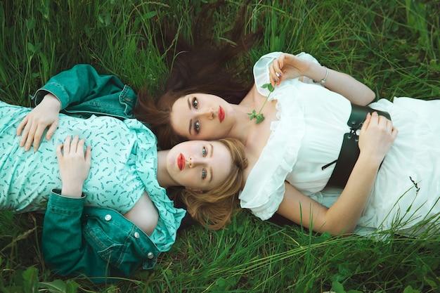 Dwie romantyczne dziewczyny leżące na łące trawy. widok z góry. nieostrość. pojęcie wolności i młodości