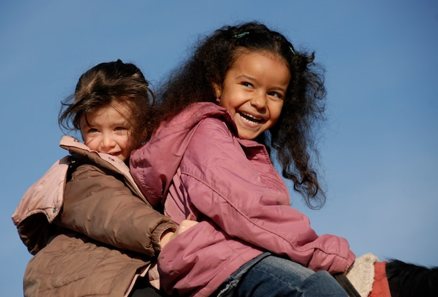 Dwie roześmiane dziewczyny na koniu