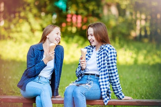 Dwie roześmiane młode kobiety dziewczyny jedzą lody w letnim parku, narodowy dzień lodów. zabawne wakacje, komunikacja z przyjacielem.