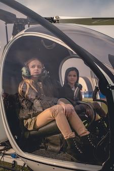 Dwie rozmarzone dziewczęta na fotelach pilota w kokpicie helikoptera