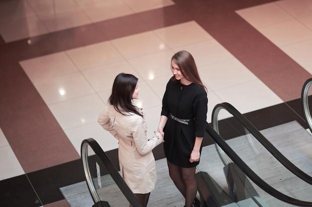 Dwie rozmawiające kobiety biznesu, stojące na schodach ruchomych w centrum biznesowym