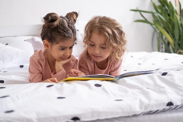 Dwie różne dzieci dziewczyny siostry przyjaciółki w piżamie czytające książkę leżącą na białej pościeli na łóżku w domu