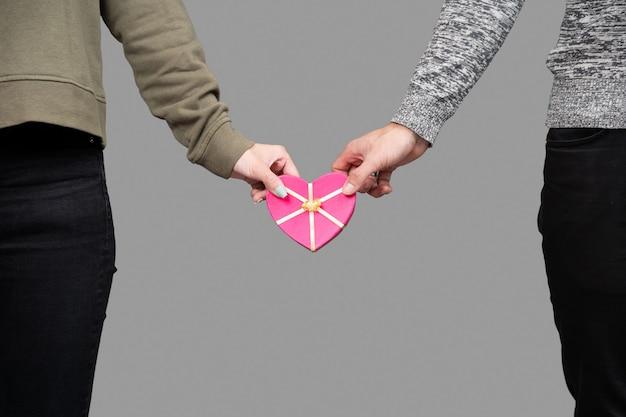 Dwie różne osoby trzymające się za ręce na szarym tle w kształcie serca