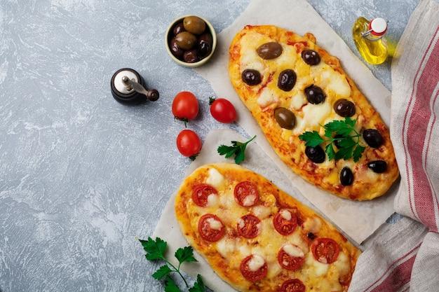 Dwie różne owalne greckie pizze z oliwkami i pomidorem margarita na szarym betonie.