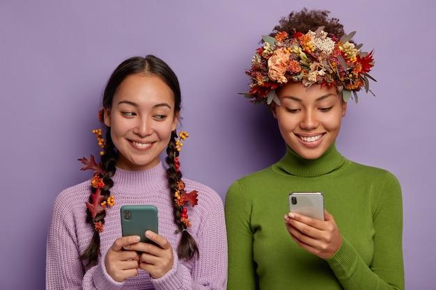 Dwie różnorodne kobiety korzystające z telefonu komórkowego z dekoracyjnymi jesiennymi liśćmi w głowach