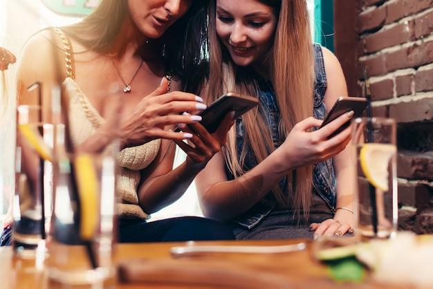 Dwie rozochocone dziewczyny używa telefon patrzeje ekran podczas gdy mieć napój przy barem