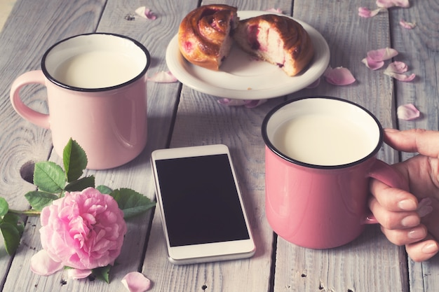Dwie różowe filiżanki z mlekiem na białym drewnianym stole