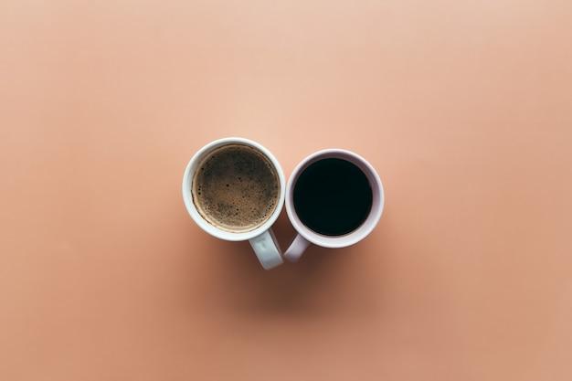 Dwie różowe i niebieskie filiżanki do kawy na beżowym tle. wysokiej jakości zdjęcie