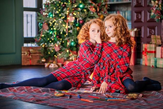 Dwie rudowłose dziewczyny z kręconymi włosami piszą list do świętego mikołaja na tle choinki i udekorowanego pokoju.