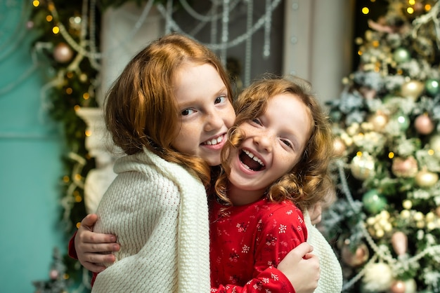 Dwie rudowłose siostry na werandzie domu udekorowanego na boże narodzenie