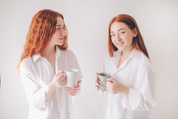 Dwie rudowłose siostry stoją na białym tle na białym tle w obszernych obszernych koszulach. dwie młode dziewczyny piją kawę lub herbatę i odbywają przyjacielską pogawędkę.