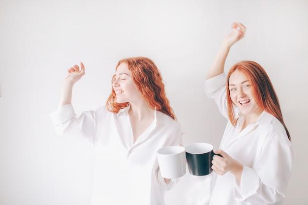 Dwie rudowłose siostry stoją na białym tle na białym tle w obszernych obszernych koszulach. dwie młode dziewczyny piją kawę lub herbatę i wygłupiają się i dobrze się bawią