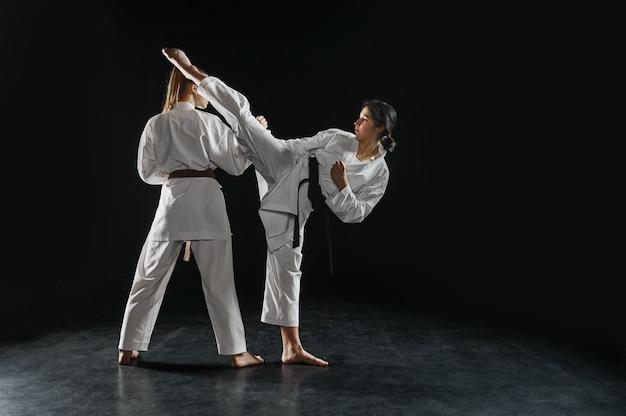 Dwie samice karatekki w białym kimonie, uderzają w akcji. zawodnicy karate na treningu, sztuki walki, zawody kobiet walczących