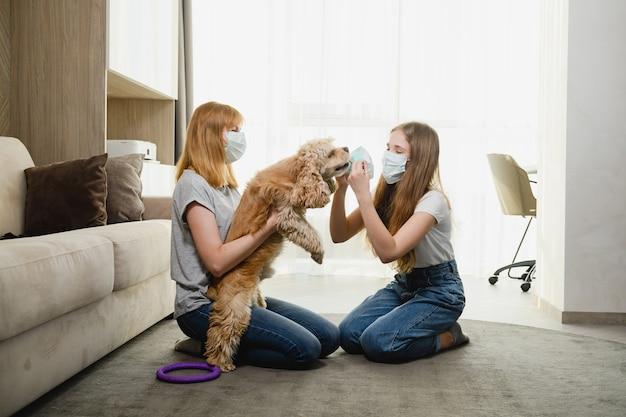 Dwie samice w domu w okresie izolacji starają się chronić uroczego zwierzaka przed wirusami, koronawirusem, pokrywającym pysk psa. mama i córka z psem.