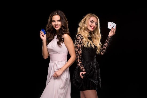 Dwie seksowne dziewczyny brunetka i blondynka, pozowanie z żetonami i kartami w rękach, koncepcja pokera. strzał studio. dwie piękne kobiety w sukienkach na czarnym tle