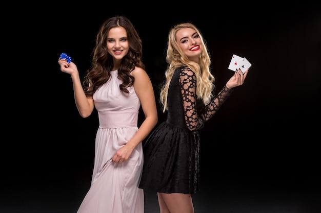 Dwie seksowne dziewczyny brunetka i blondynka pozują z żetonami w dłoniach poker koncepcja czarne tło