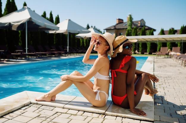 Dwie seksowne dziewczyny w kapeluszach, siedząc na skraju basenu, widok z tyłu. szczęśliwi ludzie bawią się na letnie wakacje, impreza świąteczna przy basenie na świeżym powietrzu. wypoczynek kobiet w ośrodku?