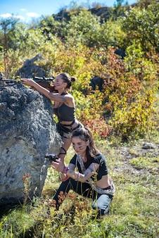 Dwie seksowne piękne młode kobiety z bronią palną w przyrodzie. przygoda