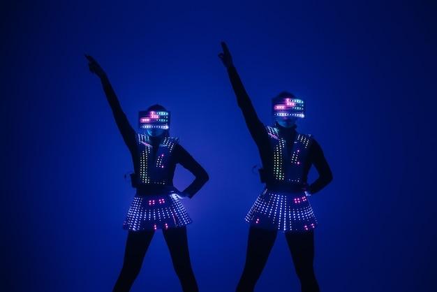 Dwie seksowne tancerki disco poruszają się w kostiumach uv. imprezy i tańce.