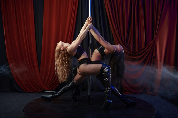 Dwie seksowne tancerki na scenie, taniec na rurze, striptiz tancerki. atrakcyjne striptizerki, taniec na kolanach, występy na rurze, gorące dziewczyny