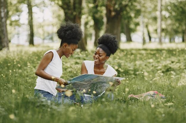 Dwie siostry afroamerykańskie patrzące na mapę w parku
