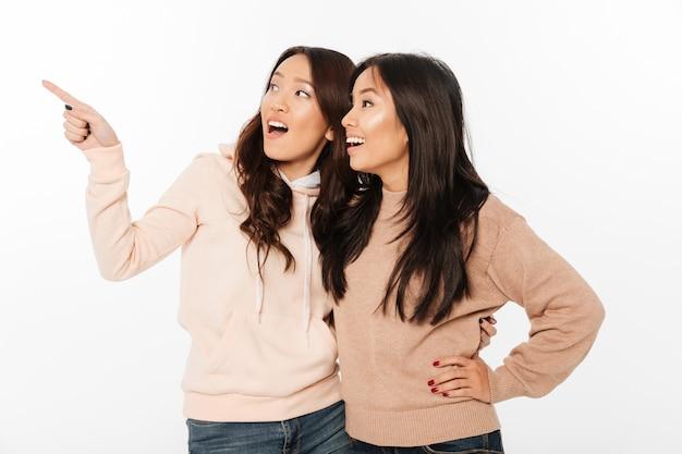 Dwie siostry azjatyckie bardzo szczęśliwy panie przytulanie, wskazując.