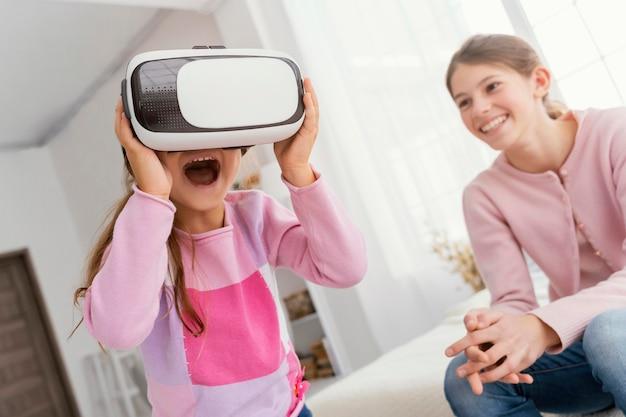 Dwie siostry bawią się w domu przy użyciu zestawu słuchawkowego do wirtualnej rzeczywistości