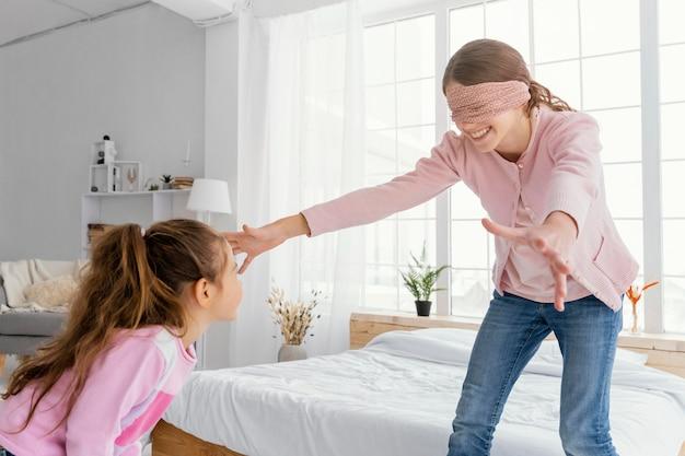 Dwie siostry bawią się w domu z zawiązanymi oczami