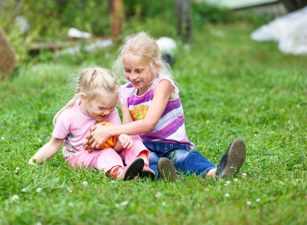 Dwie siostry bawiące się na łące z piłką
