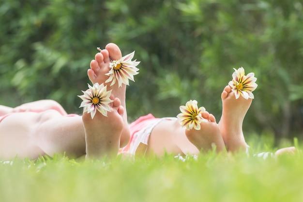 Dwie siostry bawiące się stokrotkami na trawie na świeżym powietrzu w parku, letnia zabawa