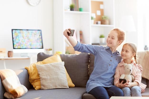Dwie siostry biorące selfie w domu