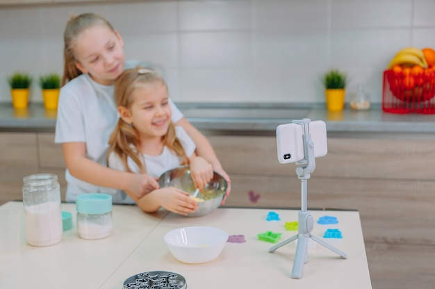 Dwie siostry blogerki gotują w kuchni i kręcą kulinarny film na smartfonie.