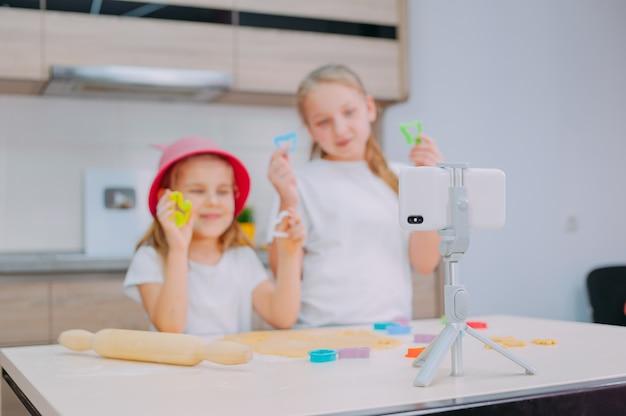 Dwie siostry blogerki przygotowują ciasteczka w kuchni i kręcą kulinarne wideo na smartfonie.
