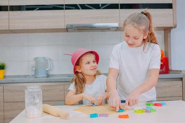 Dwie siostry blogerki przygotowują ciasteczka w kuchni.