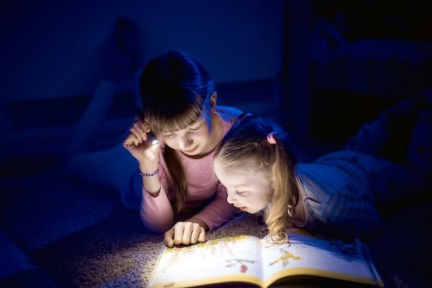 Dwie siostry czytające książkę z latarką w ciemnym pokoju w nocy