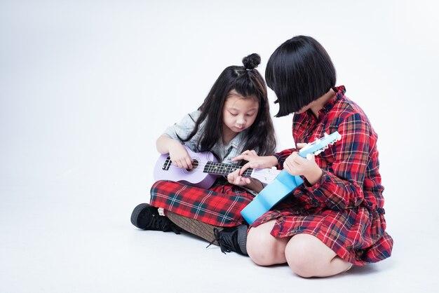 Dwie siostry grają ukulele razem, starsza siostra uczy młodszą siostrę