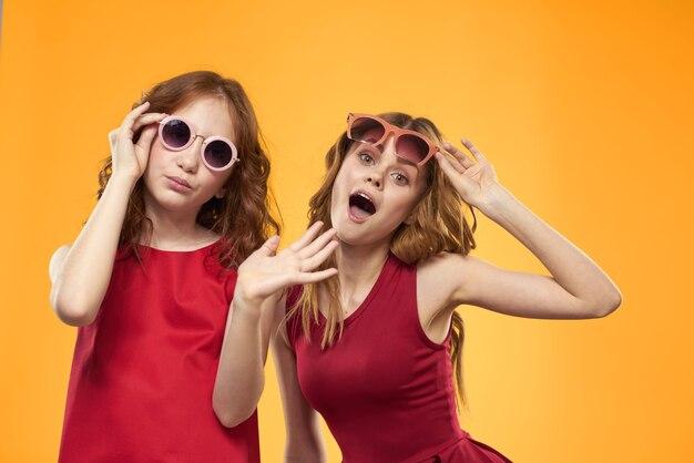 Dwie siostry i zabawne okulary przeciwsłoneczne moda przyjaźń żółta rodzina