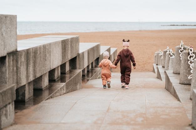 Dwie siostry idą ręka w rękę nad morze. starsza siostra opiekuje się młodszym. dzieci spacerują nad morzem.