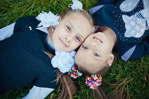 Dwie siostry leżą na trawie i z uśmiechem patrzą w kamerę
