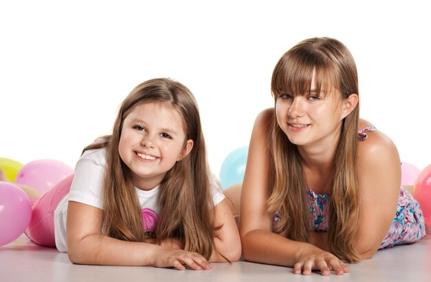 Dwie siostry leżące na podłodze z balonami