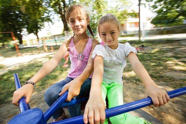Dwie siostry na karuzeli na placu zabaw