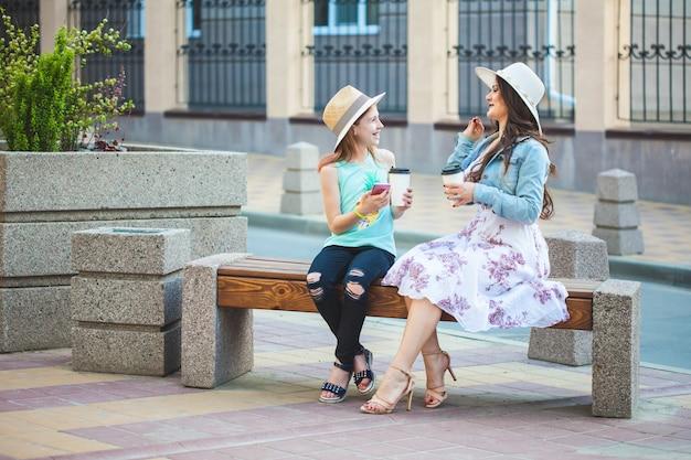 Dwie siostry, piękna brunetka i młoda dziewczyna spacerująca po mieście, siedząca na ławce z kawą w rękach i rozmawiająca, śmiejąca się