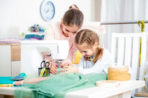 Dwie siostry pracujące na maszynie do szycia