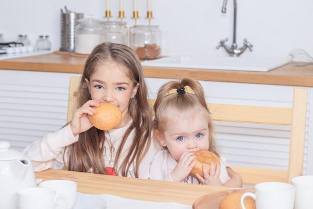 Dwie siostry przy stole jedzące chleb. przekąska. dziewczyny jedzą. jasna kuchnia.