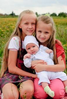 Dwie siostry przytulają się i braciszek na dworze, szczęśliwa rodzina