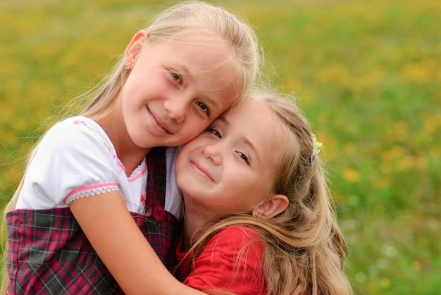 Dwie siostry przytulają się na zewnątrz, szczęśliwa rodzina