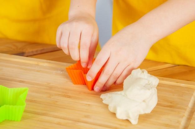 Dwie siostry rasy kaukaskiej przygotowują ciasteczka w kuchni za pomocą drewnianej deski do krojenia, wałka do ciasta i foremek.